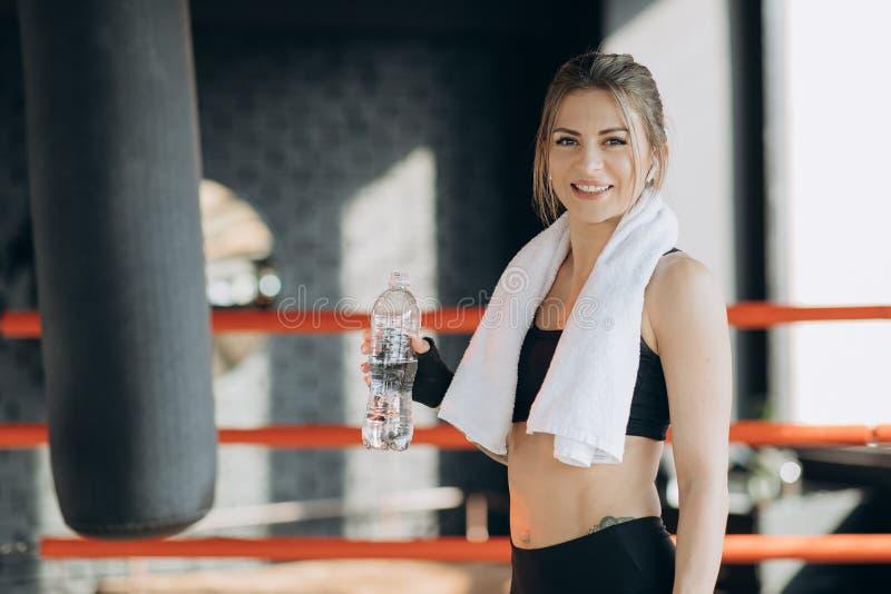可爱的体育女孩微笑的和饮用水,当站立在健身类时 库存照片