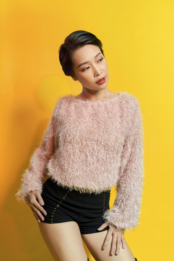 可爱的妇女表现出真实的正面情感在photoshoot期间用桃红色毛皮大衣 活跃迷人的女孩室内画象  免版税库存照片