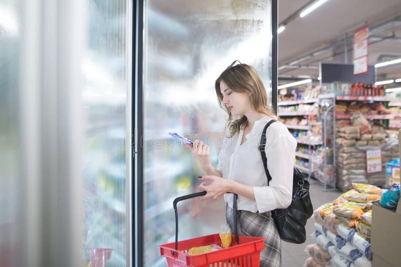 可爱的年轻女人在他的手上站立在冰箱在商店用冷冻食品 库存照片