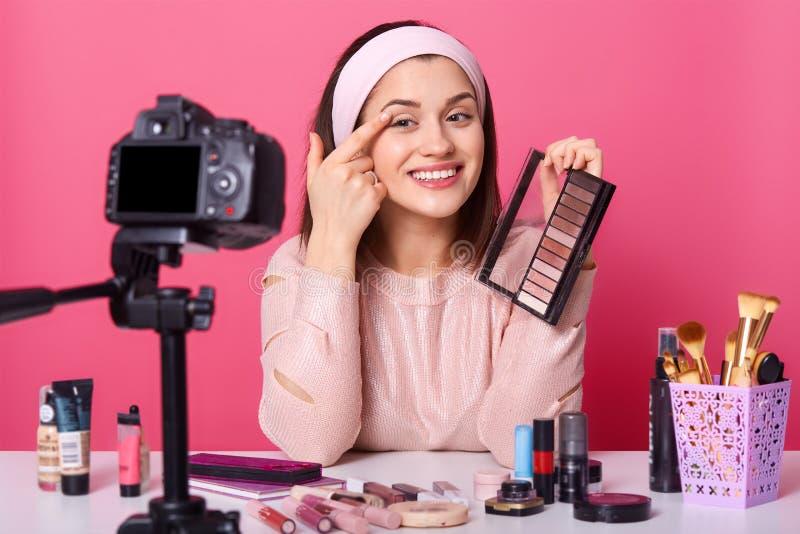 可爱的年轻女人通过互联网挣钱,在被修理的照相机前面坐三脚架,应用眼影膏,有快乐 免版税库存图片