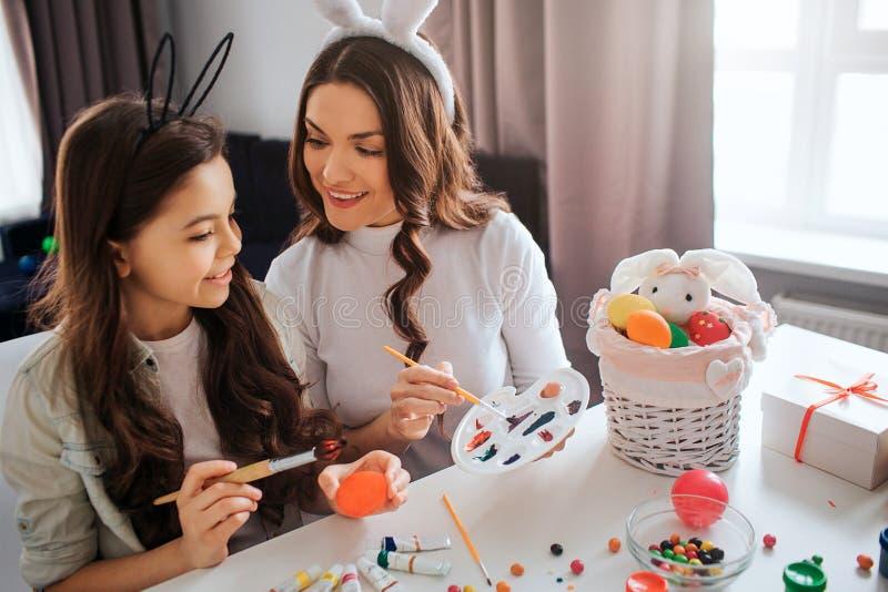 可爱的母亲和女儿为复活节做准备 他们在屋子里绘鸡蛋 女孩举行刷子 在pallete的母亲点 免版税库存照片