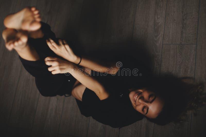 可爱的性感的妇女在地板上说谎 女孩看起来愉快和微笑 说谎在与腿的地板上的妇女 库存照片
