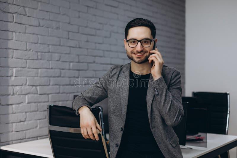 可爱的英俊的年轻深色的有胡子的微笑的行政工作者人在事务驻地职场,谈话电话的 免版税库存图片
