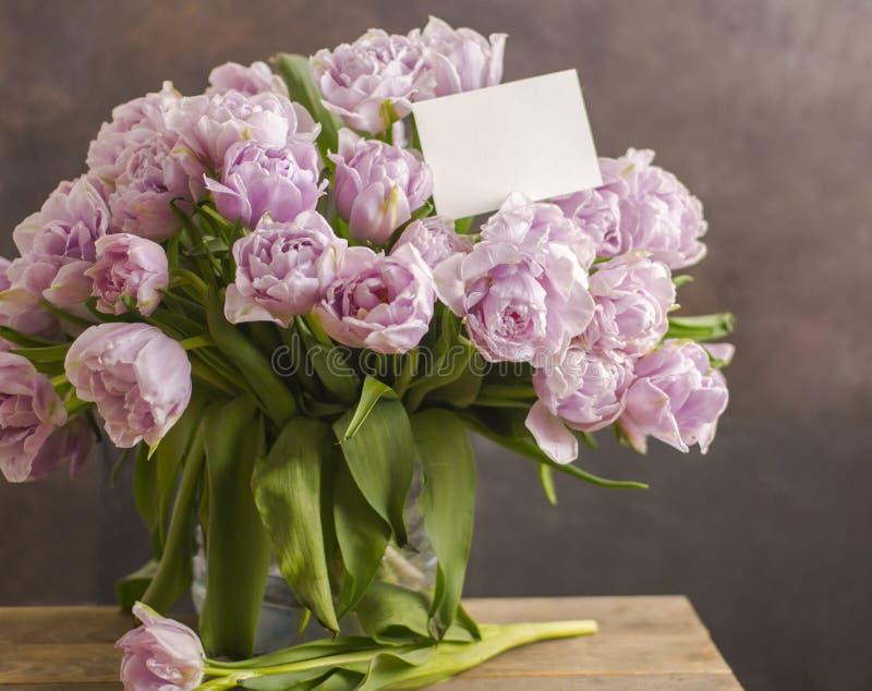 双重紫罗兰色郁金香花美丽的大花束与空白的贺卡的在黑暗的rustik背景 文本嘲笑的地方 免版税库存照片