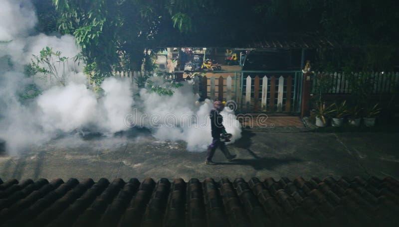 发布烟的人清理蚊子和在晚上保护疟疾在村庄 库存照片