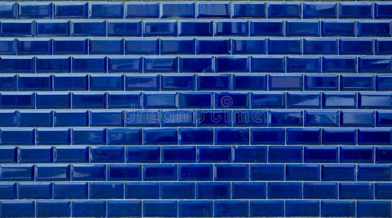 发光的蓝色砖铺磁砖在外墙上的背景纹理 库存图片