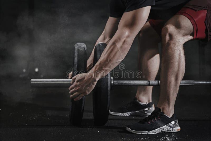 发怒适合的运动员特写镜头为举的重量做准备在健身房 杠铃氧化镁保护 做功能t的帅哥 免版税库存照片