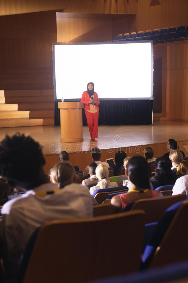 发表在观众前面的女实业家讲话在观众席 库存图片