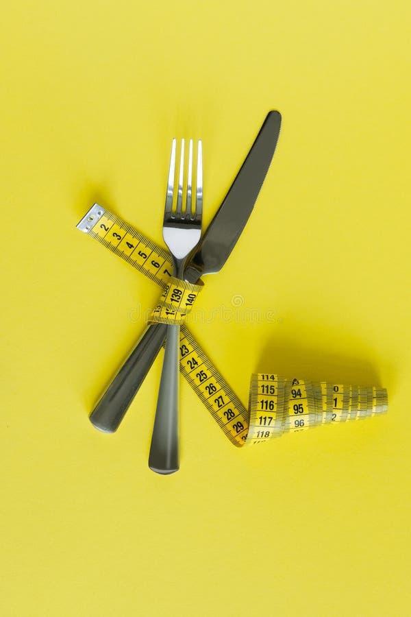 叉子和刀子在黄色背景的磁带线路包裹了 概念饮食 库存图片