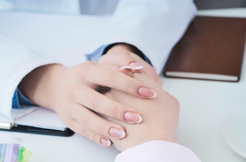 友好的女性医生递握坐在鼓励,同情,欢呼和支持的书桌的耐心手 库存图片