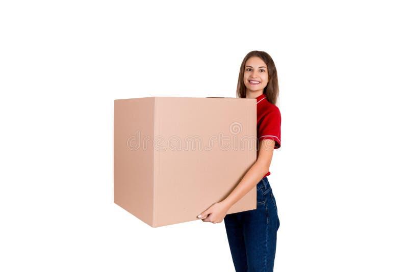 友好的年轻delivey女孩带来在白色背景隔绝的顾客的一个大小包 库存图片