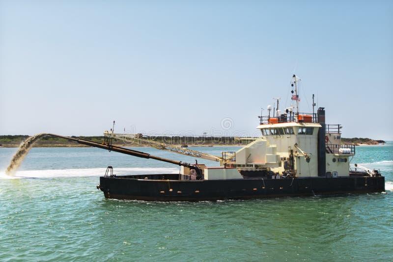 取消沙子和泥沙的挖泥机小船从底部 撒粉瓶船工作 库存照片