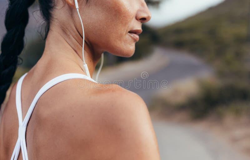 听到音乐的妇女在锻炼期间 库存图片