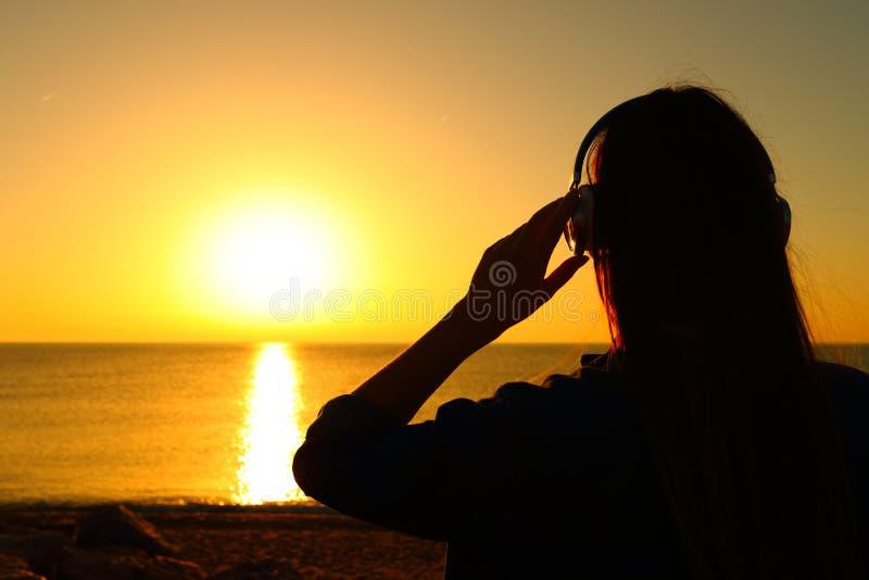 听的妇女使音乐变冷在日落 免版税库存图片