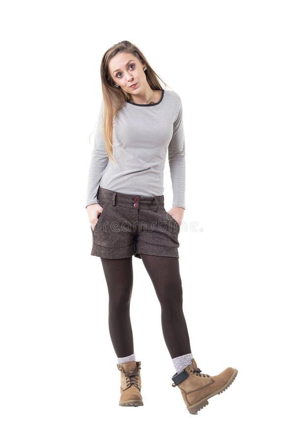吹口哨用在口袋的手的凉快的年轻白肤金发的妇女cutie 免版税图库摄影