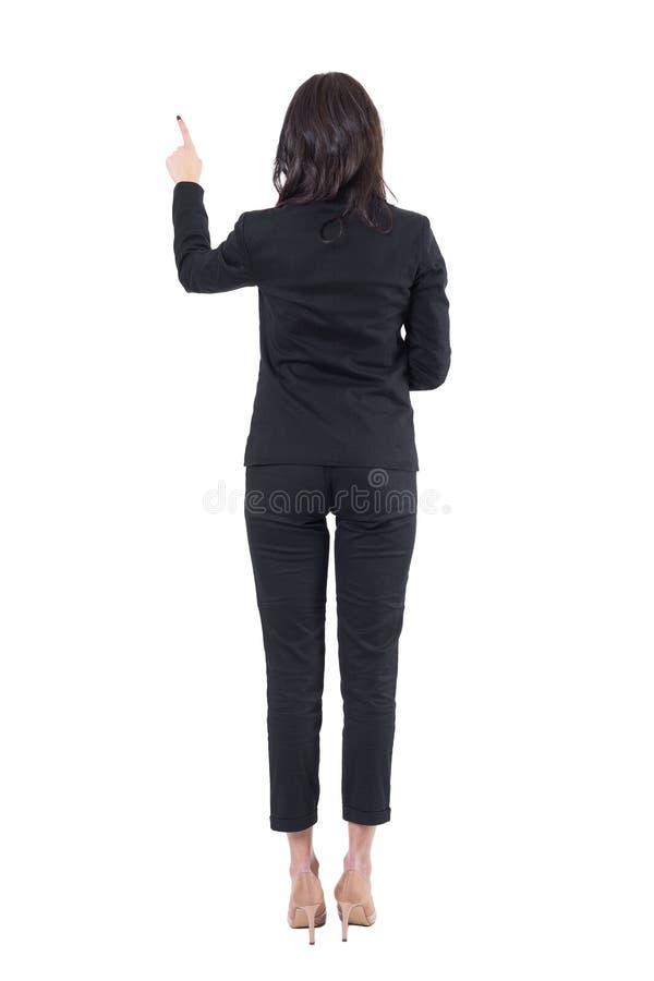 后面观点的使用屏幕按钮的用左手的典雅的女商人 库存图片