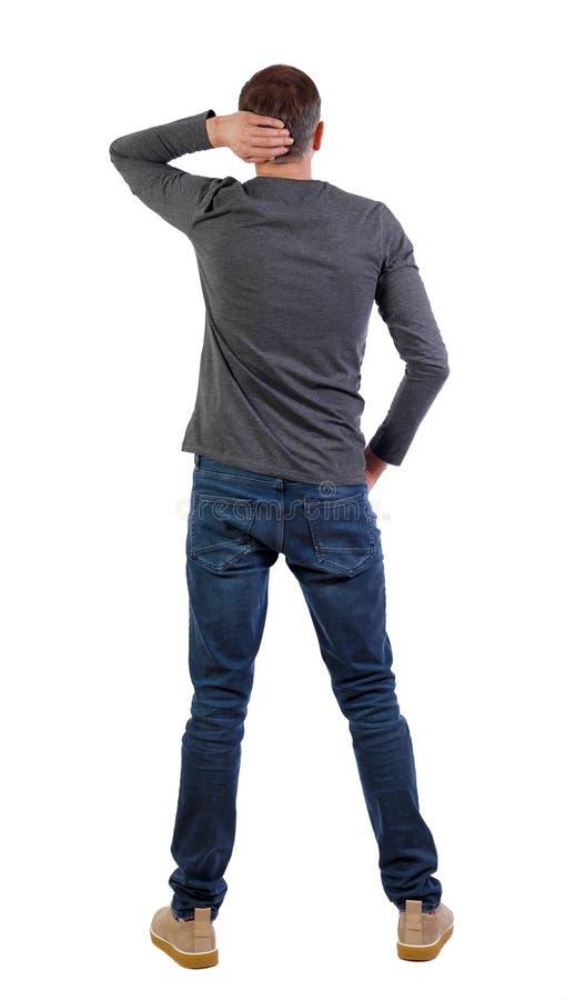 后面观点的牛仔裤的人 常设年轻人 免版税库存照片