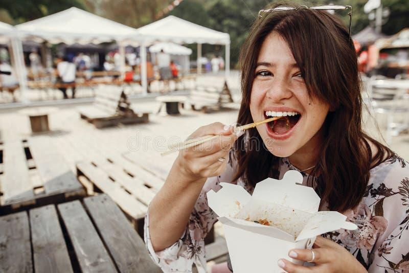 吃与菜的时髦的行家女孩铁锅面条从有竹筷子的纸盒箱子 亚洲街道食物节日 Boho 库存照片