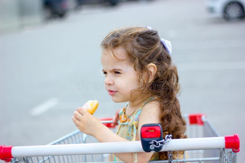 吃多福饼的小女孩在购物中心停车处 免版税库存照片