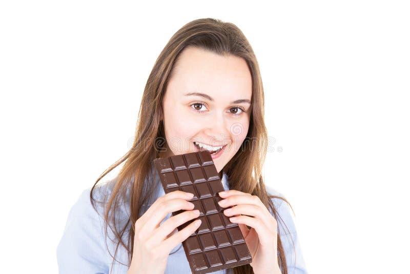 吃巧克力块的年轻女人画象反对白色背景 免版税库存照片