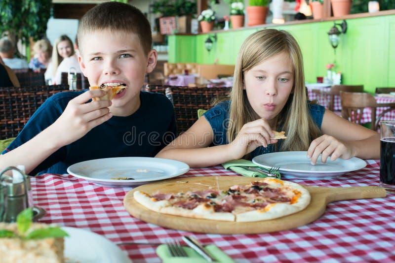 吃在咖啡馆的愉快的少年比萨 朋友或兄弟姐妹获得乐趣在餐馆 免版税库存图片