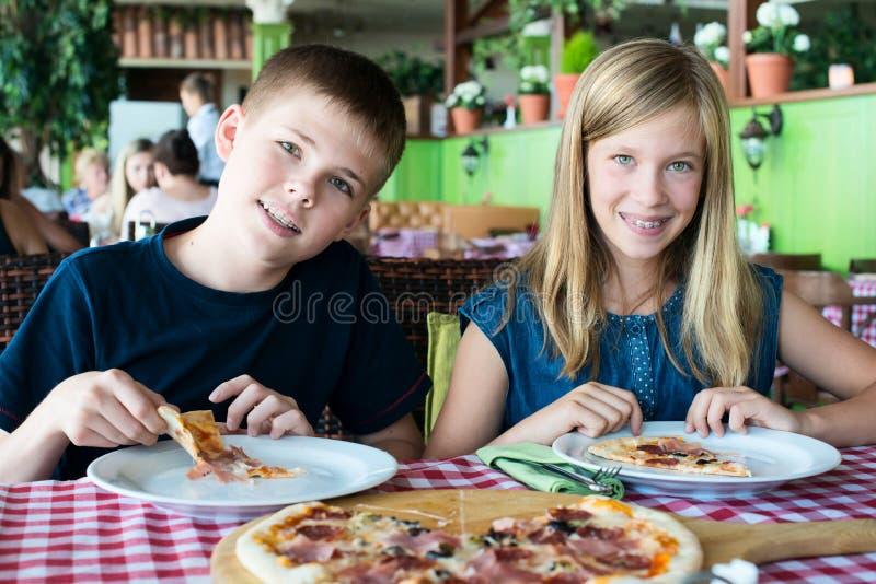 吃在咖啡馆的愉快的少年比萨 朋友或兄弟姐妹获得乐趣在餐馆 库存照片