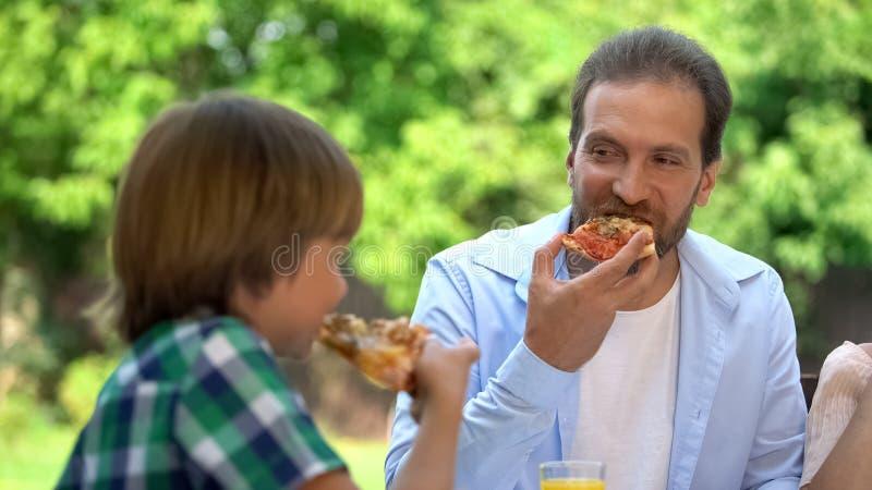 吃在咖啡馆,喜爱的食物,家庭周末的儿子和父亲鲜美比萨 库存图片