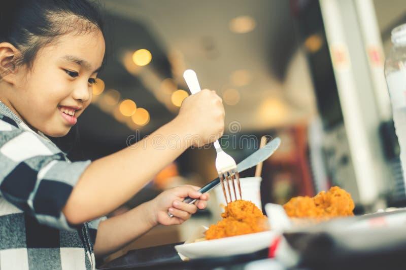 吃炸鸡美食广场的亚裔孩子 免版税库存图片