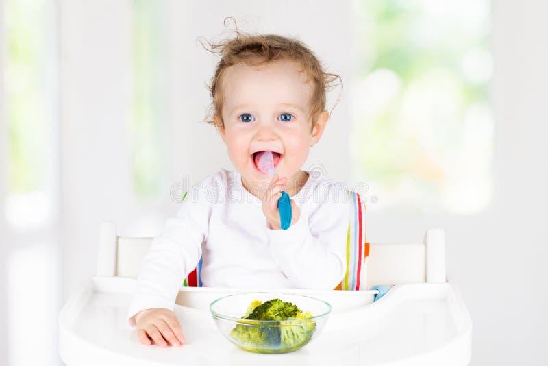 吃菜的婴孩 婴儿的坚实食物 免版税库存图片