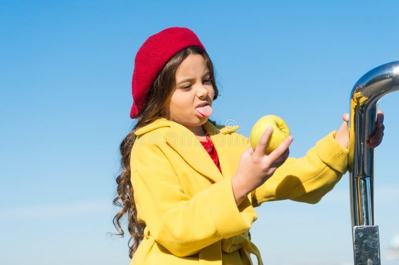 吃这滋补食物是坚硬部分 吃果子食物的逗人喜爱的儿童怨恨 咬住入酸绿色的女孩 免版税库存照片