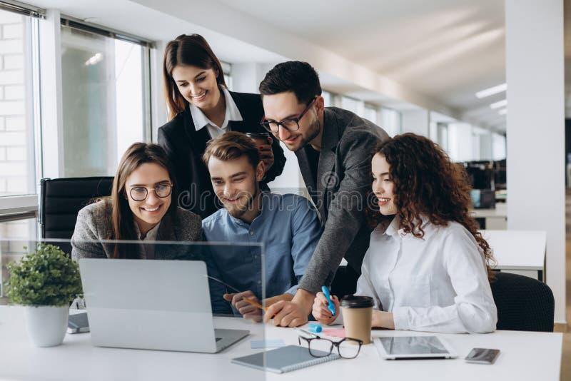 合作是钥匙对成功 谈论年轻的商人某事,当一起看计算机显示器时 免版税库存图片