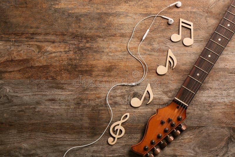 吉他脖子、耳机和音乐笔记关于木背景,平的位置 库存照片