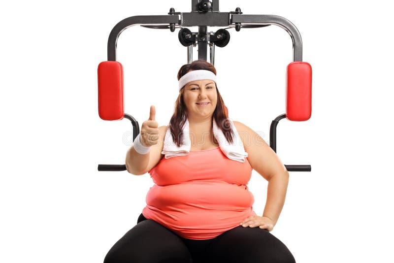 坐一个多功能健身房机器和显示赞许的超重年轻女人 免版税库存照片