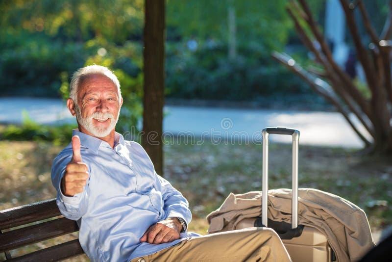 坐一个长木凳和放松在公园的资深绅士 免版税库存照片