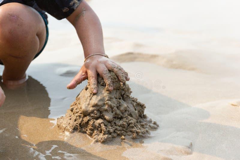 坐亚裔的孩子演奏沙子在假日在海 库存照片