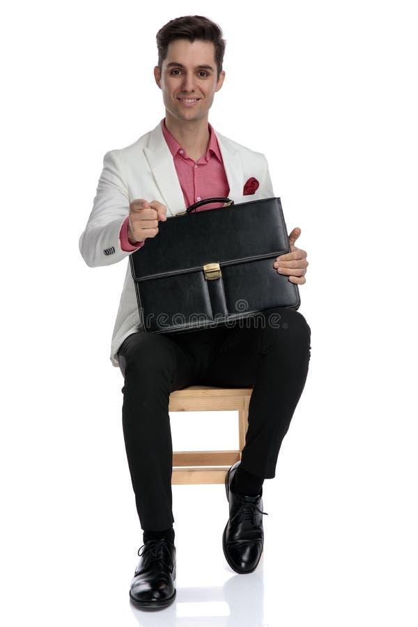 坐带着手提箱和指向手指的年轻典雅的人 免版税库存图片