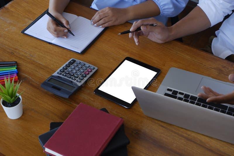 坐在上司旁边的女性秘书采取在企业惯例-图象的办公室概念的笔记下 库存图片