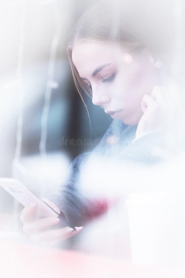 坐在一个咖啡馆的少女的画象与调查电话的街道的反射的窗口外 免版税图库摄影
