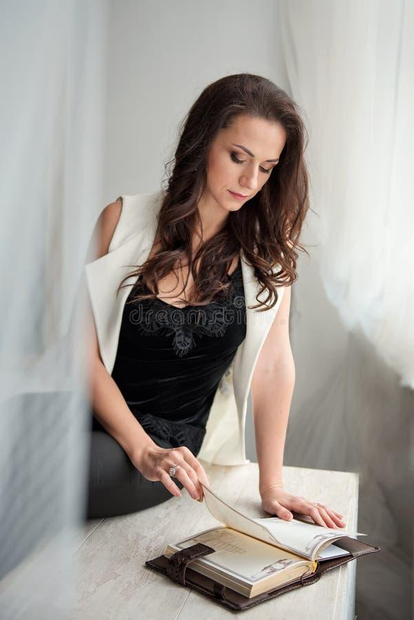 坐在一个白色织品机盖下和周道地看日志的美丽的深色的妇女 库存图片