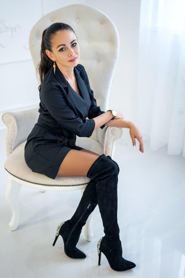 坐在一把白色椅子的美丽的时髦的确信的妇女在演播室 免版税图库摄影