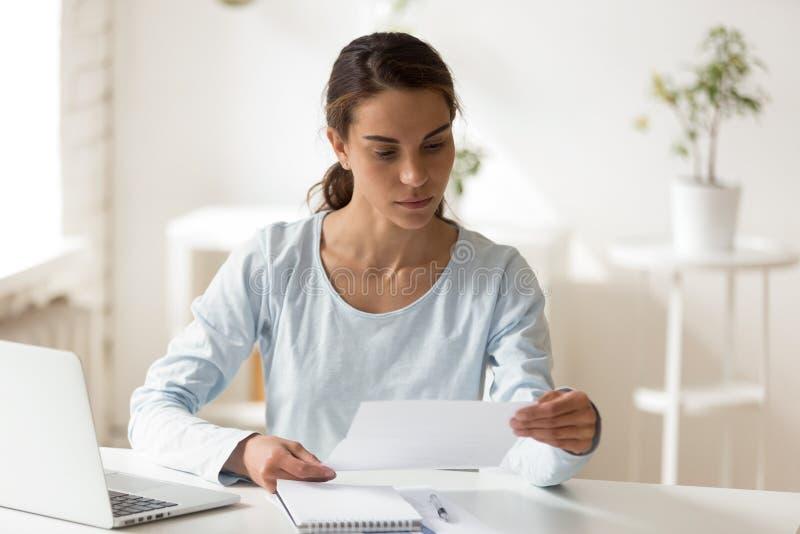 坐在书桌读书信件的严肃的妇女 免版税库存照片