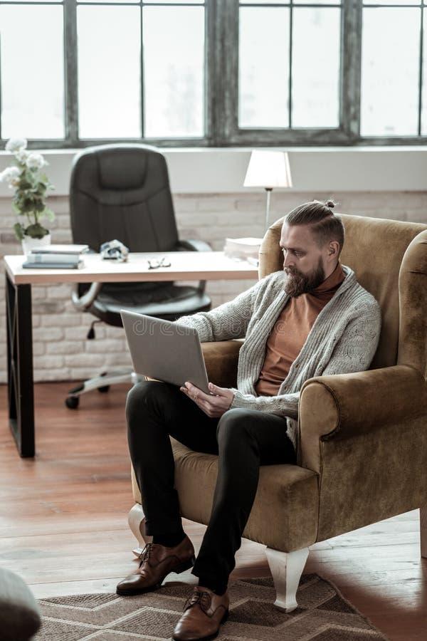 坐在他屋子和工作里的老练的聪明的心理学家 免版税库存图片