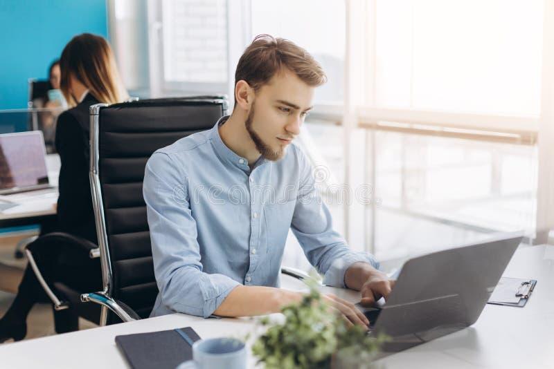 坐在他的书桌的年轻人画象在办公室 免版税库存图片