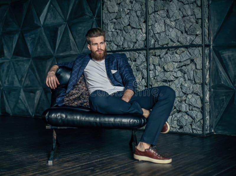 坐在他的工作场所的体贴的年轻时髦人士 免版税库存照片