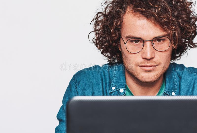 坐在他的有膝上型计算机的书桌的严肃的年轻人画象 运作在办公室的白种人商人的特写镜头图象 免版税库存图片