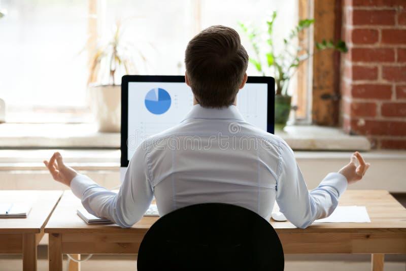 坐在做瑜伽的个人计算机对面的书桌的背面图商人 免版税库存照片