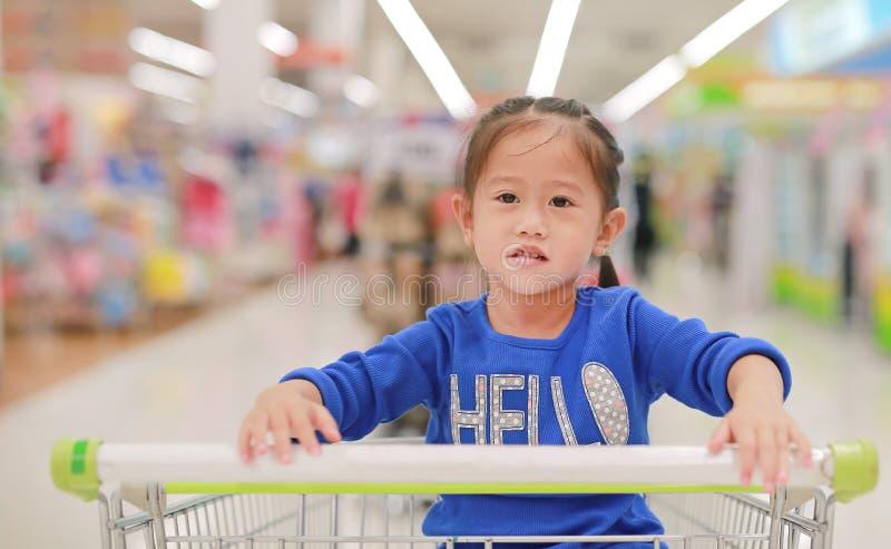 坐在台车的亚裔小孩女孩在家庭购物期间在市场上 图库摄影