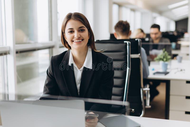 坐在她的工作场所的一名愉快的女实业家的画象在办公室 库存图片