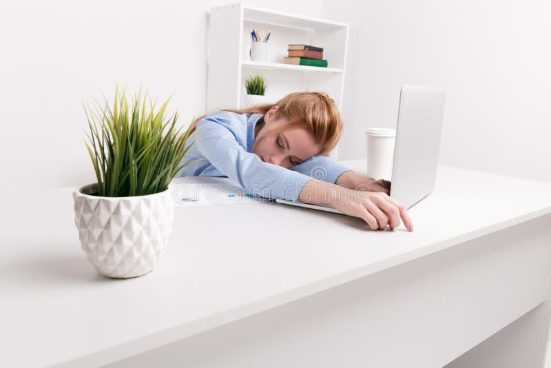坐在她的工作场所的年轻女勤杂工感到坏 妇女有头疼 查找疲乏 库存图片