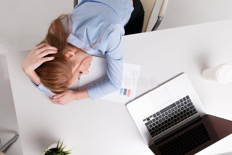 坐在她的工作场所的年轻女勤杂工感到坏 妇女有头疼 库存照片